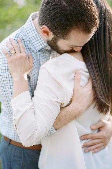 couple embracing man kissing woman's shoulder