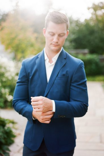 man posing fixing his cufflinks in a blue suit