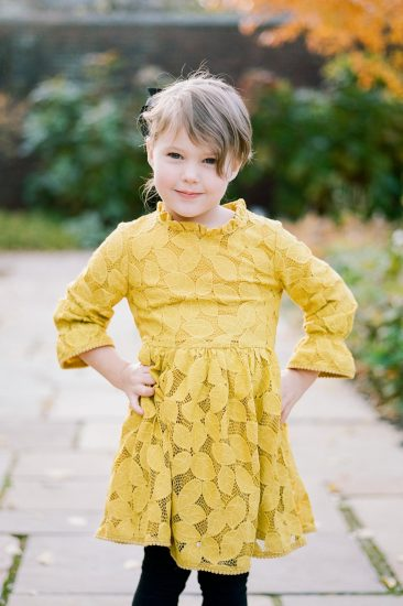 young girl posing for her picture in a yellow lace dress