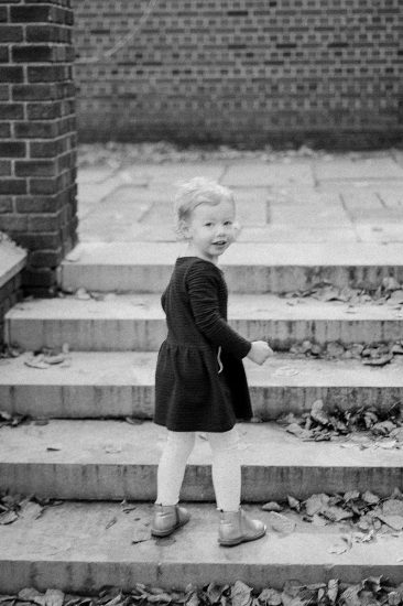 Black and white photo of a little girl walking up steps in a park