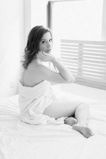 Black and white image of a woman sitting on a bed wrapped in a sheet