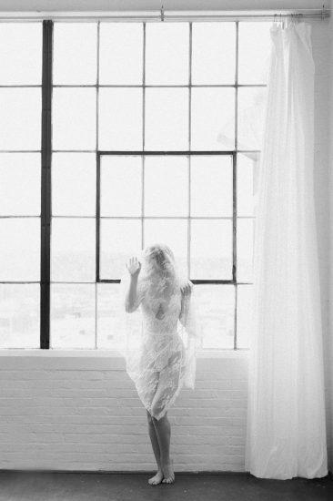 woman with lace veil over her body near a window black and white photo