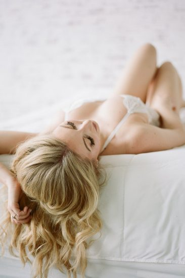 woman laying on a bed in a white laced one piece
