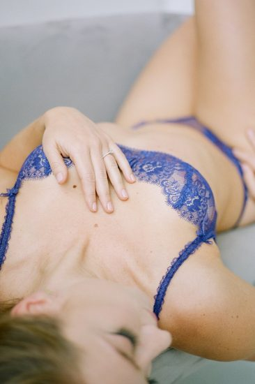 woman laying on a grey couch in blue lingerie