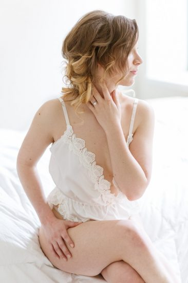 woman sitting on the edge of a bed in a white vintage romper