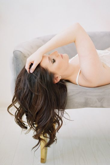 side view of a woman with her hands through her hair laying on a grey couch