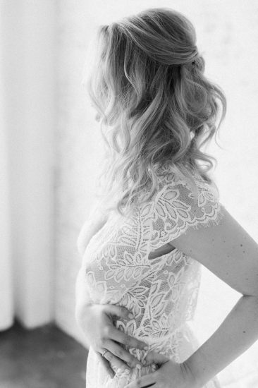 side view of a woman wearing a white lace romper