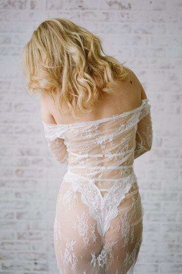 woman wearing a white lace body suite and robe