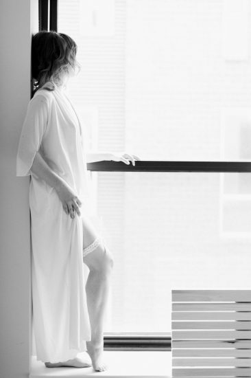 woman standing on a window sill in white vintage robe