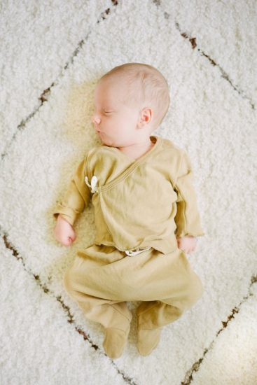 Newborn baby laying on a white shag carpet sleeping