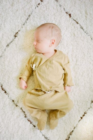 Newborn baby laying on a white shag carpet sleeping