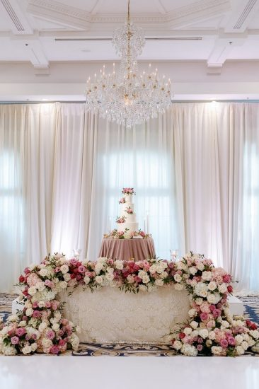 Pink and white flowers covering the head table with wedding cake at reception