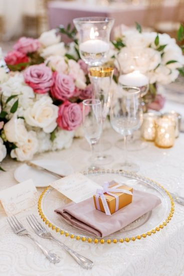 Place setting with gold rimmed china and pink and white flowers