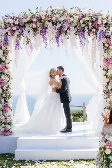 Bride and groom kissing at their ceremony under a chuppah covered with pink and white flowers