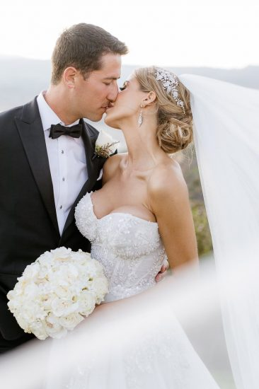 Bride and groom kissing with bride's veil in portrait