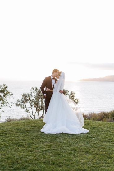 bride and groom standing on the cliff side of the California coast at sunset