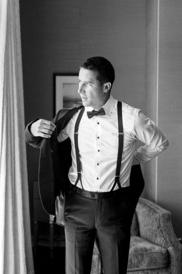 Groom putting on his tuxedo black and white photo