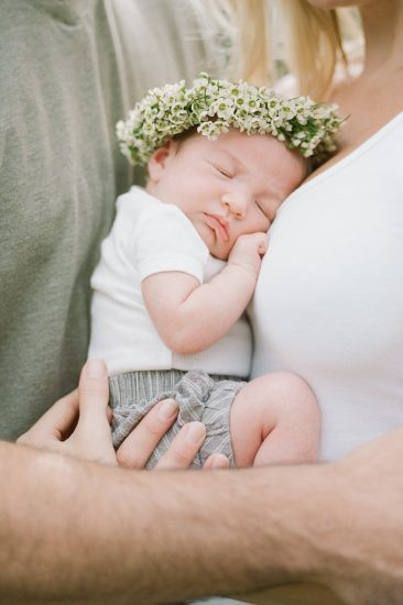 newborn baby wearing a flower crown and white onsie