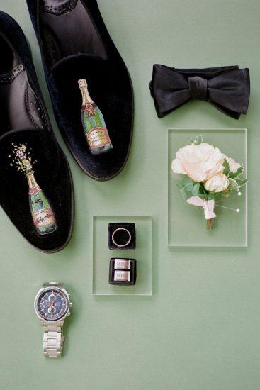 groom's details black tux velvet shoes with champagne bottle