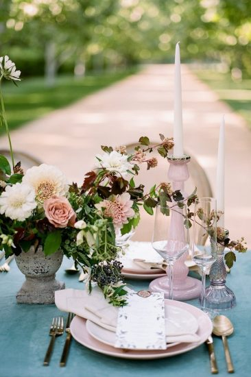 table set up with candle sticks and pink plates with a blue velvet table cloth