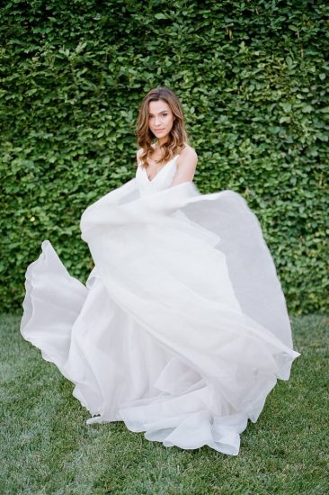 bride wearing a carol hannah bridal gown while dancing in the grass