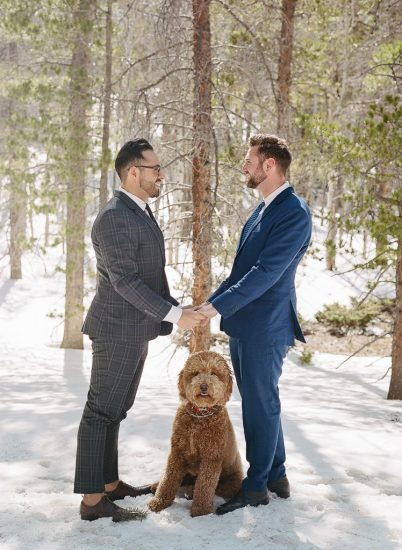 Estes Park Engagement Photography Session - two gay men holding hands in the snow with their dog