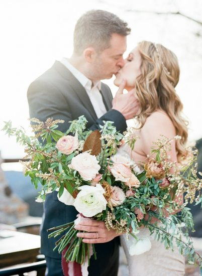couple kissing in the California sunlight holding a bouquet