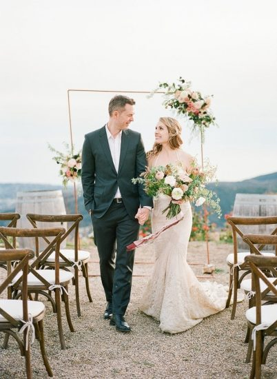 Couple walking down the aisle bride wearing an inbal dror gown and holding bouquet