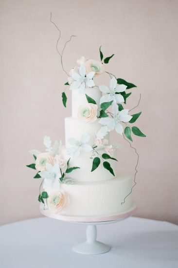 white cake with sugar flower designs of light blue and pink