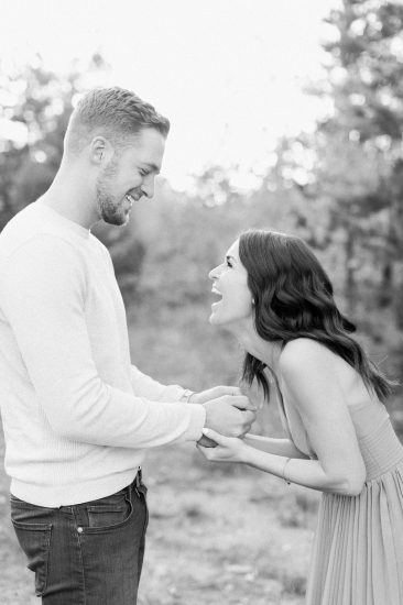 Couple laughing together while holding hands black and white photo