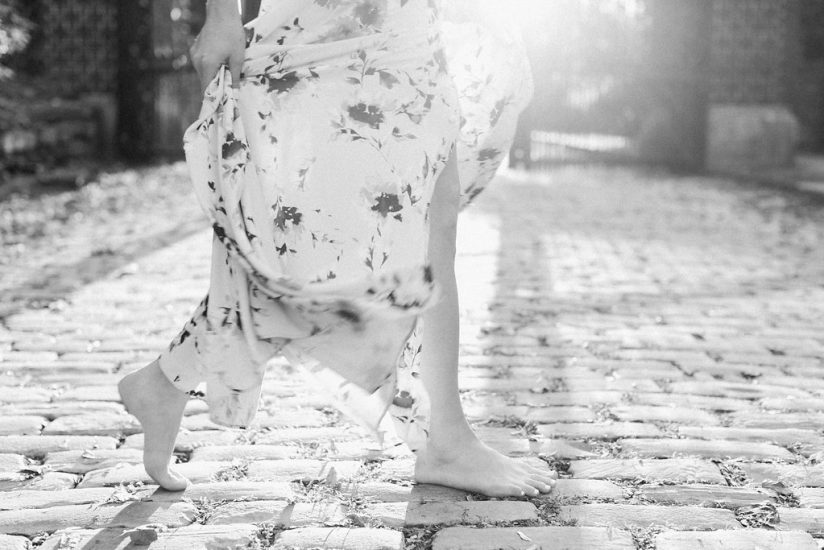 black and white photo of woman walking on cobblestones
