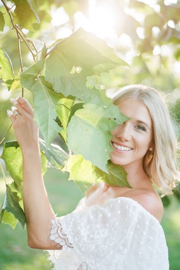 Beautiful blue eyes and blonde hair woman standing under a tree with leaves around her wearing white ruffled show me your mumu dress